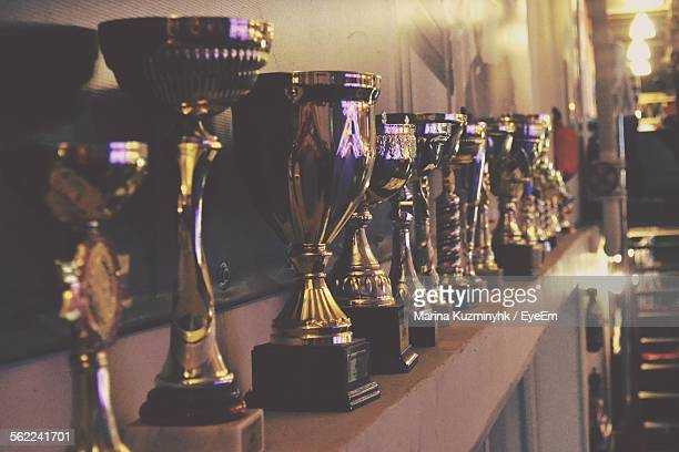 close-up of trophy on shelf against wall - award stock pictures, royalty-free photos & images