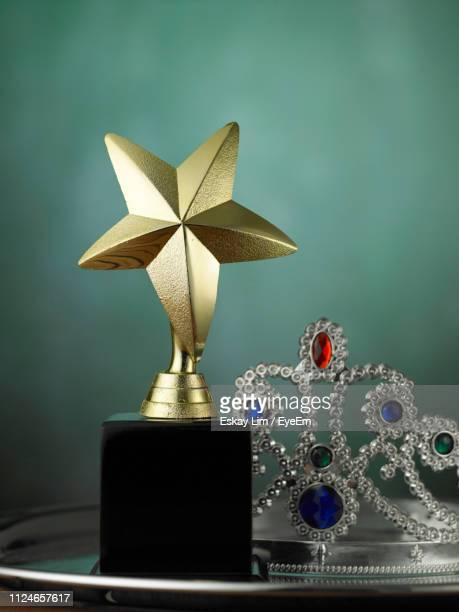 close-up of trophy on table against gray background - crown close up stock pictures, royalty-free photos & images