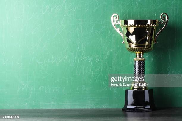 Close-Up Of Trophy On Table Against Green Scribbled Wall