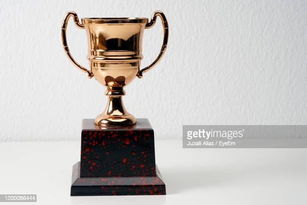 close-up of trophy on table - trophy stock pictures, royalty-free photos & images