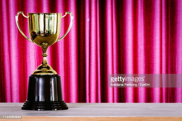 close-up of trophy on wooden table against curtain - trophy stock pictures, royalty-free photos & images