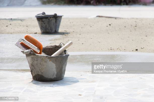 close-up of trowel in bucket on footpath - bucket stock pictures, royalty-free photos & images