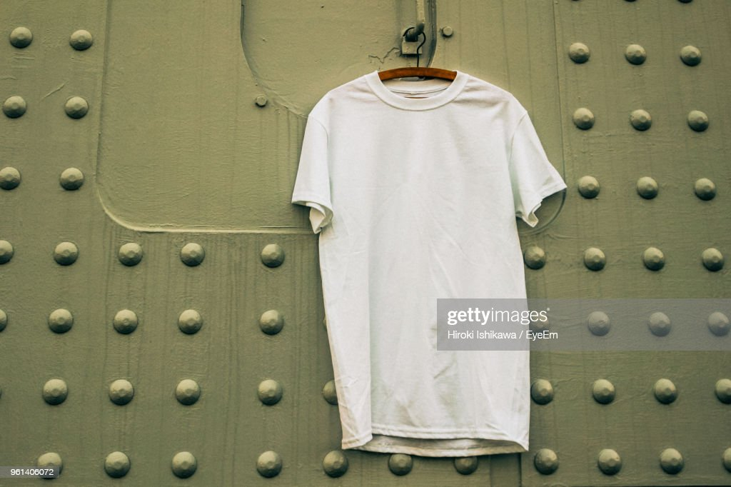 Close-Up Of T-Shirt Hanging Against Patterned Wall : Stock Photo