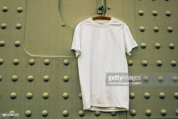 close-up of t-shirt hanging against patterned wall - maglietta foto e immagini stock