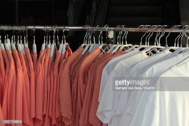 close-up of t-shirts on coathanger for sale in store - clothes rack stock pictures, royalty-free photos & images