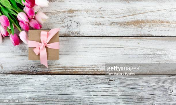 Close-Up Of Tulips And Gift On Wooden Table