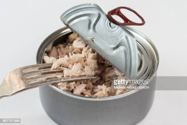 Close-Up Of Tuna In Container Against White Background