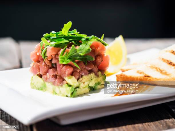 Close-Up Of Tuna Tartare With Avocado In Tray Against Black Background