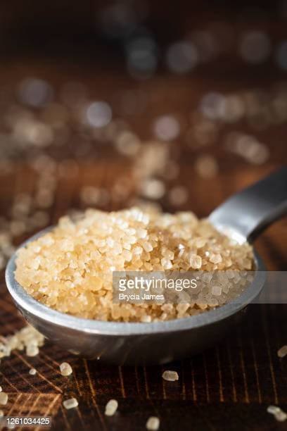 closeup of turbinado sugar on a teaspoon - brycia james stock pictures, royalty-free photos & images