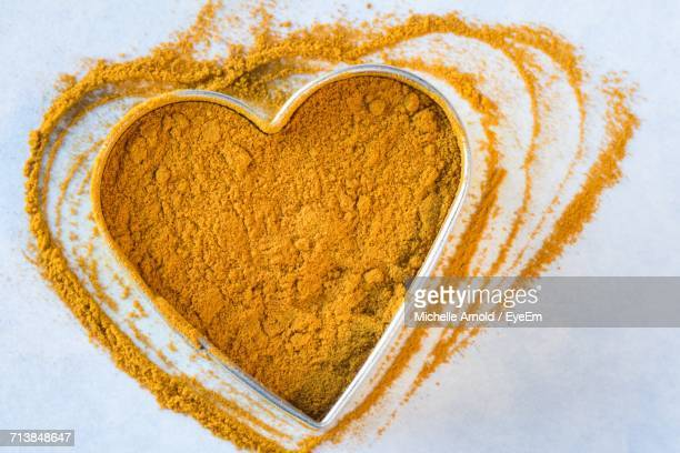 Close-Up Of Turmeric In Heart Shape Container On Table