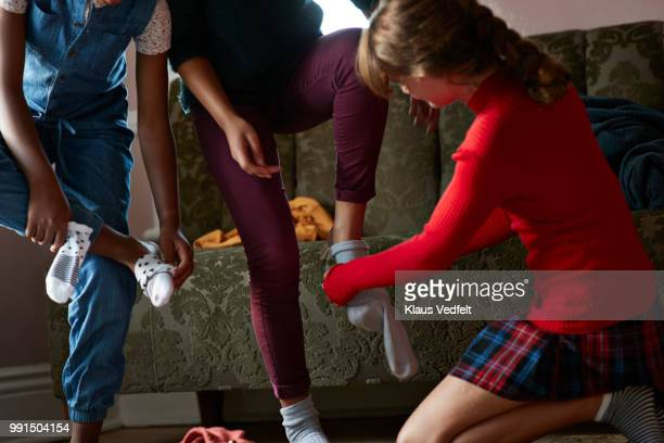Close-up of tween girls trying clothes and putting on socks, at home