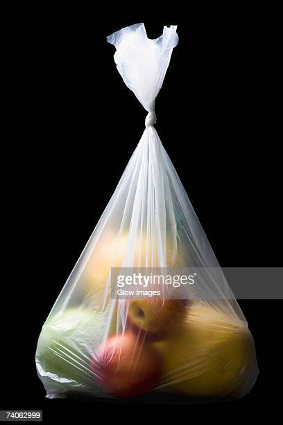 Close-up of two apples and three oranges in a plastic bag