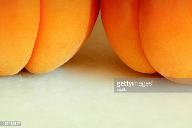 Close-up of two apricots on a white table