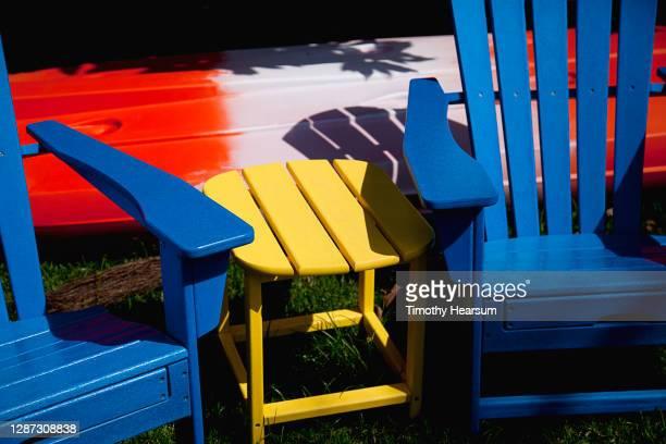 close-up of two blue adirondack chairs, yellow table and red/white kayak - timothy hearsum bildbanksfoton och bilder