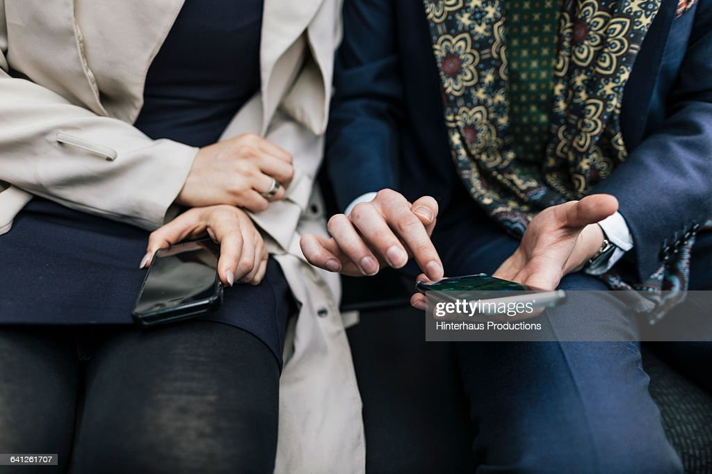 Close-up of two business checking smartphones : Stock Photo