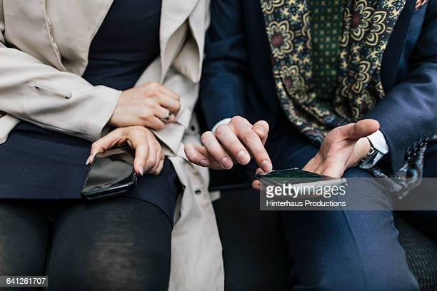Close-up of two business checking smartphones