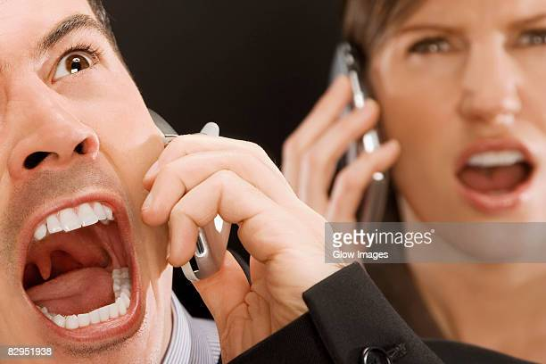 close-up of two business executives shouting on mobile phones - uvula stock photos and pictures