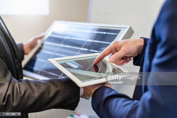 close-up of two businessmen in office with solar cell and tablet - green suit stock pictures, royalty-free photos & images