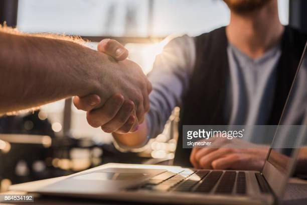 Close-up of two businessmen shaking hands after successful agreement.