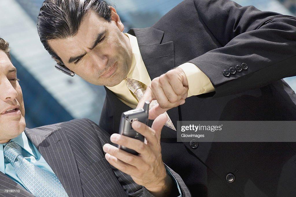 Close-up of two businessmen using a palmtop : Foto de stock