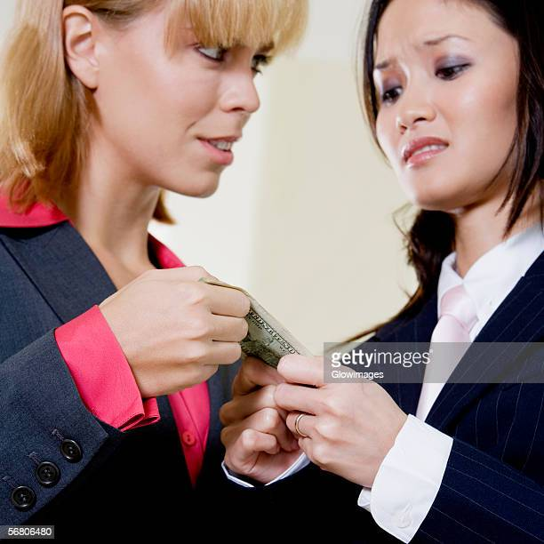 Close-up of two businesswomen holding a dollar bill