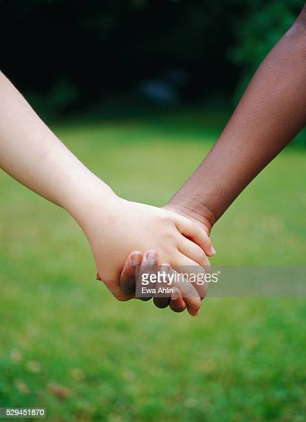 Close-up of two children holding hands