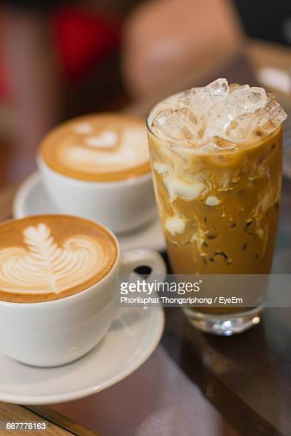 Close-Up Of Two Coffee Cups And An Iced Coffee