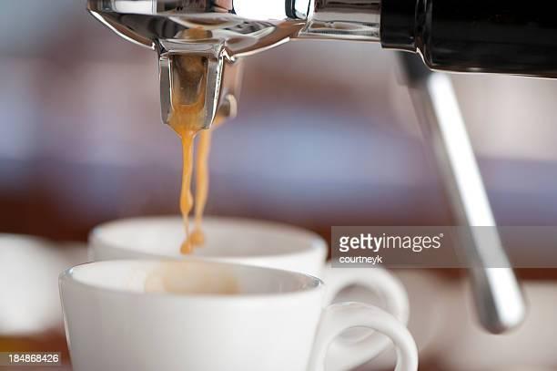 Primer plano de dos tazas de café en una cafetera para café expresso