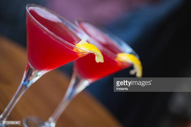 Close-up of two Cosmopolitan martinis on a Paris sidewalk bar patio.