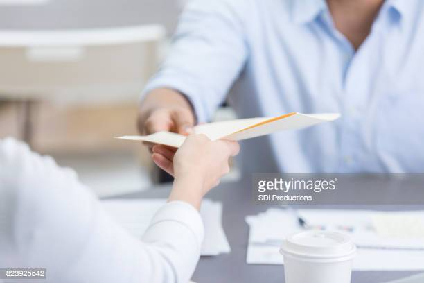 Closeup of two coworkers passing folder across table