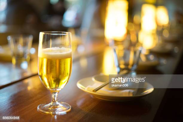 Close-up of two cups with beer glass out by business man using smart-phone after work in the pub