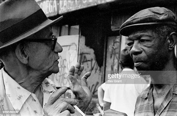Closeup of two elderly men as they talk on a sidewalk in the El Barrio neighborhood East Harlem New York New York July 1969 The photo was taken...