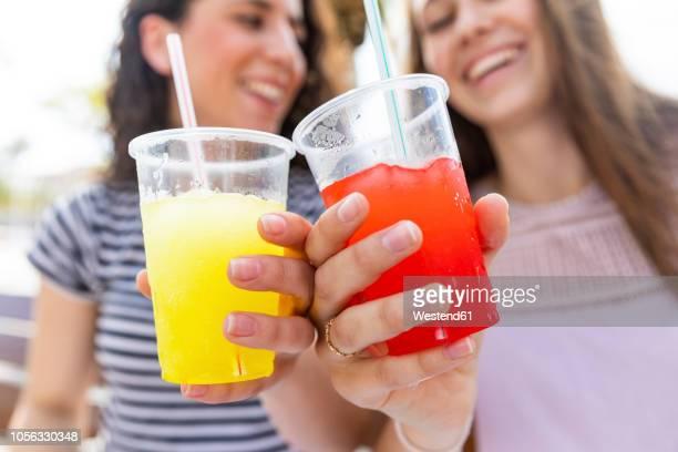 close-up of two female friends enjoying a fresh slush - slush stock photos and pictures