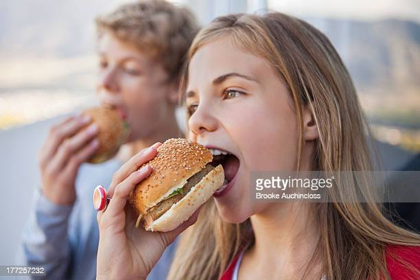Close-up of two friends eating hamburger
