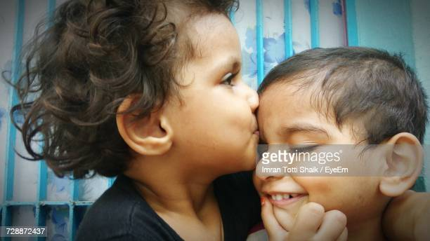 close-up of two funny children - indian girl kissing stock photos and pictures