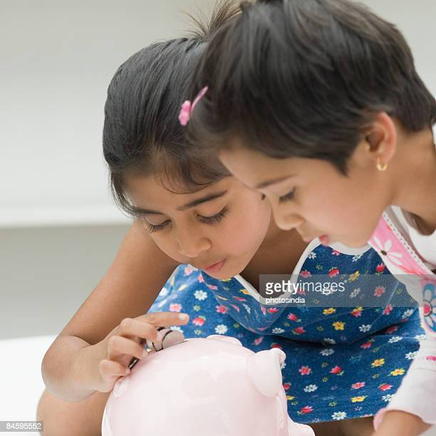 Close-up of two girls inserting coins into a piggy bank