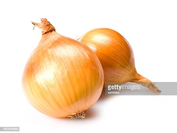 Close-up of two gold onions on white