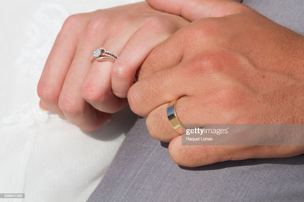 Close Up Of Two Hands Clasped Wearing Wedding Rings Stock Photo