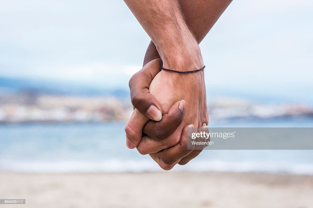 Close-up of two hands connected on the beach : Foto de stock