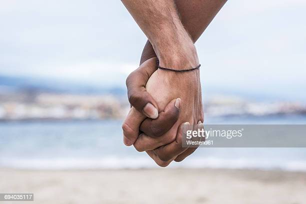 close-up of two hands connected on the beach - de mãos dadas - fotografias e filmes do acervo