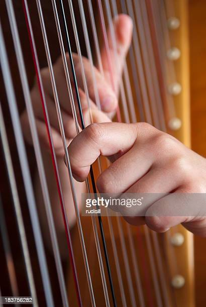 Close-up of two hands playing the harp