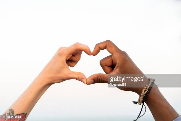 close-up of two hands shaping a heart - bracelet stock pictures, royalty-free photos & images
