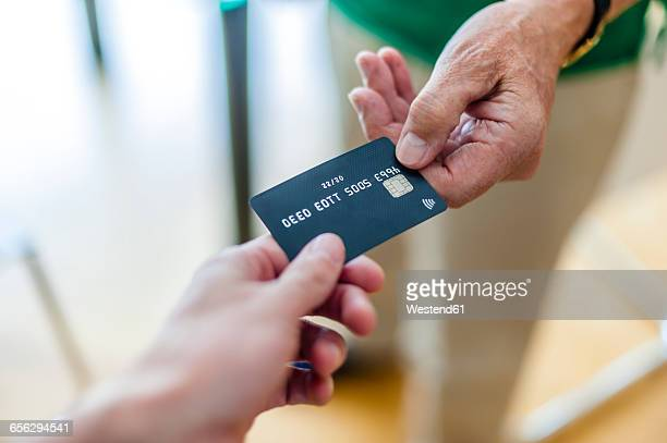 Close-up of two hands with credit card