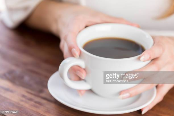 Closeup of two hands wrapped around coffee cup on table