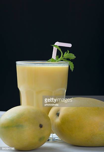 Close-up of two mangoes with a glass of mango shake