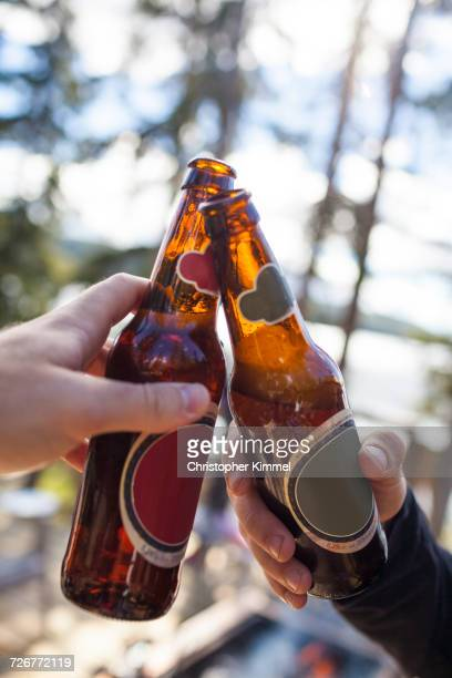 Close-up Of Two Men Toasting With Their Beer Bottles