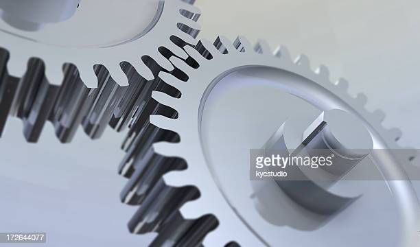 Close-up of two metal gears over silver background