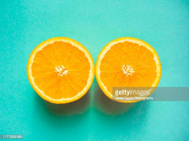 close-up of two orange halves against turquoise background - bisected stock pictures, royalty-free photos & images