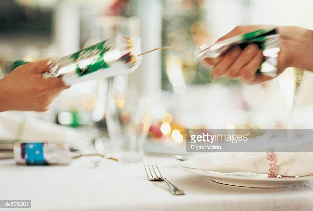 close-up of two people pulling a cracker over christmas dinner - クリスマスクラッカー ストックフォトと画像