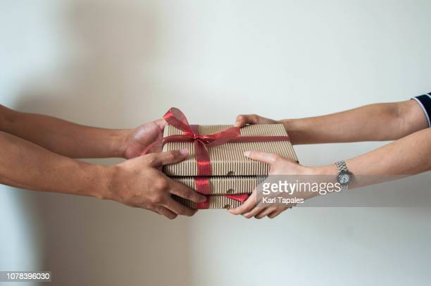 close-up of two persons sharing gifts - gift icon stock photos and pictures